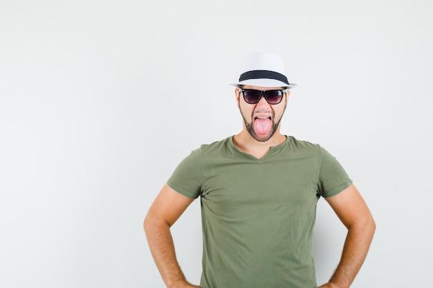 Młody mężczyzna wystający język w zielonej koszulce i kapeluszu i wyglądający na szalonego