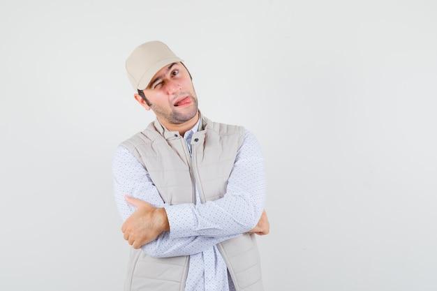Młody mężczyzna wystawiający język, trzymając ręce skrzyżowane w koszuli, kurtce bez rękawów, czapce i wyglądając na szalonego. przedni widok.