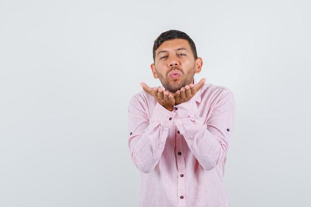 Młody mężczyzna wysyłający pocałunek powietrza na dłonie w widoku z przodu różowej koszuli.