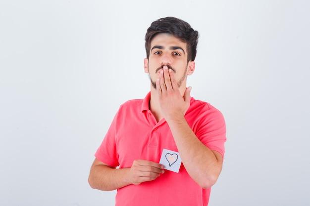Młody mężczyzna wysyłający pocałunek ręką w t-shirt i wyglądający ładny, widok z przodu.