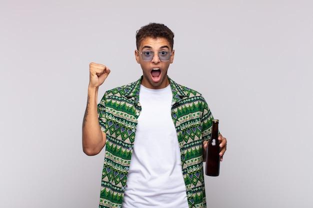 Młody mężczyzna z ameryki południowej agresywnie krzyczy z gniewnym wyrazem twarzy lub z zaciśniętymi pięściami świętując sukces