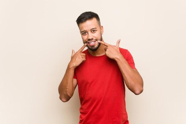 Młody mężczyzna z azji południowej uśmiecha się, wskazując palcami na usta.