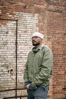 Młody mężczyzna z bandażem na głowie stojący przy ścianie z cegły