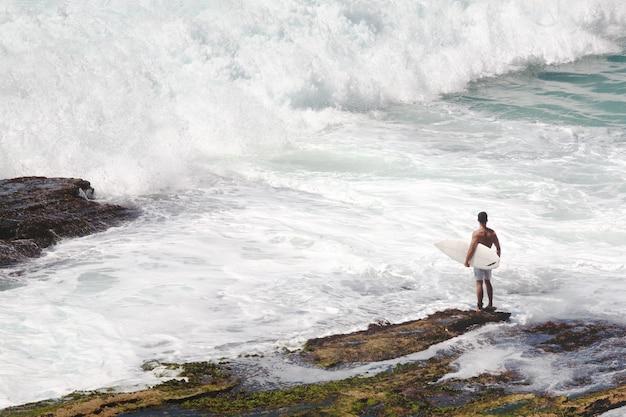Młody mężczyzna z białym biurkiem chce surfować w morzu z bardzo dużymi falami