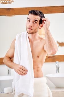 Młody mężczyzna z białym ręcznikiem na ramieniu stojący przy lustrze w wannie
