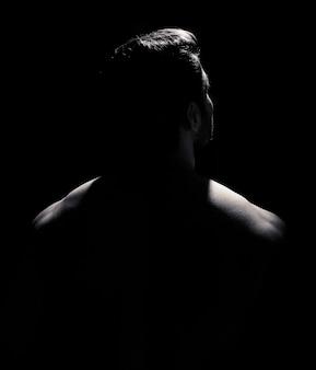 Młody mężczyzna z bliska portret z długim cieniem na czarnym tle lowkey