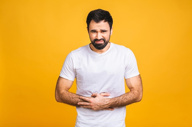 Młody mężczyzna z bólem, trzymając się za bolący brzuch na białym tle na żółtym tle. ból brzucha.