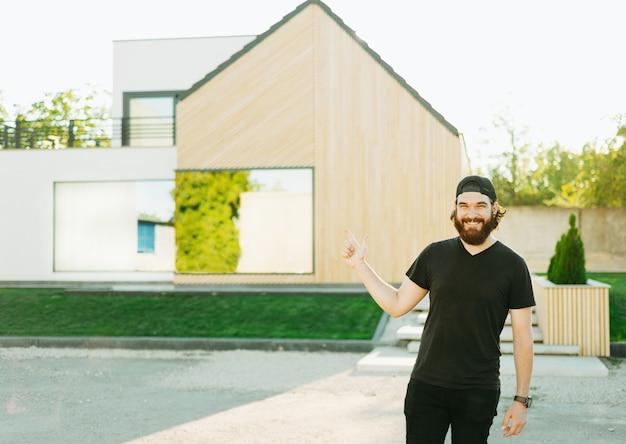 Młody mężczyzna z brodą i wskazujący na swój nowy dom z tyłu