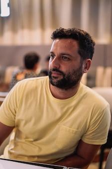 Młody mężczyzna z brodą i żółtą koszulką