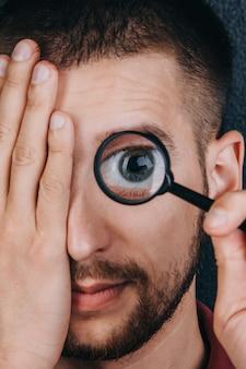 Młody mężczyzna z brodą patrzy przez szkło powiększające.