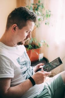 Młody mężczyzna z brodą siedzi na łóżku i pracuje z domu na tablecie. digitalizacja. pracuj online. szkolenie online. zostań w domu w czasie kwarantanny. słoneczny dzień w domu. nieostrość