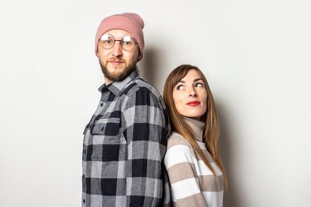 Młody mężczyzna z brodą w kapeluszu i kraciastej koszuli oraz dziewczyna w swetrze stoją tyłem do siebie