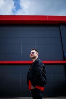 Młody mężczyzna z brodą w okularach w czerwonej modnej koszulce z kurtką pozuje w pobliżu szarego budynku. atrakcyjny facet odpoczynek w mieście w letni dzień. moda męska.
