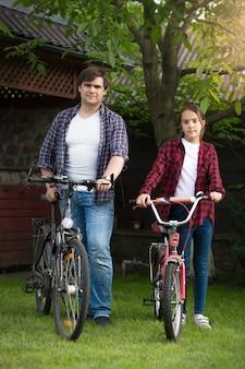 Młody mężczyzna z córką jedzie na rowerach w parku