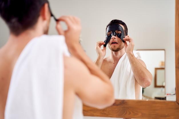Młody mężczyzna z czarną maską na twarzy stojący rano w wannie naprzeciwko lustra