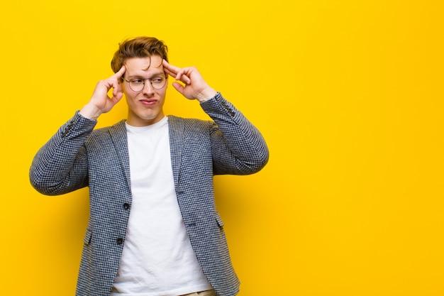 Młody mężczyzna z czerwoną głową, skoncentrowany i intensywnie zastanawiający się nad pomysłem, wyobrażający sobie rozwiązanie problemu lub problemu