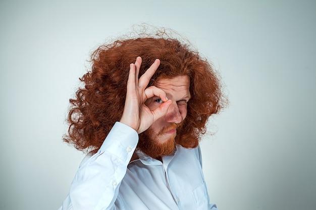 Młody mężczyzna z długimi rudymi włosami patrząc w kamerę, mrużąc oczy