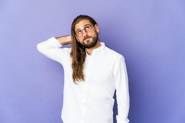 Młody mężczyzna z długimi włosami, dotykając tyłu głowy, myśląc i dokonując wyboru.