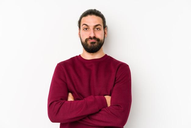 Młody mężczyzna z długimi włosami na białym tle na białej ścianie niezadowolony z sarkastycznego wyrazu.