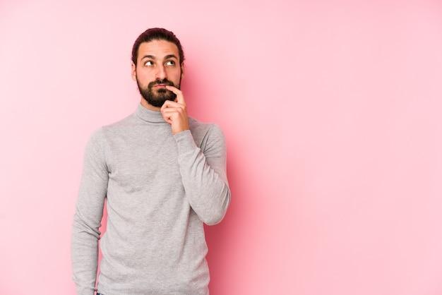 Młody mężczyzna z długimi włosami odizolowany na różowej ścianie, patrząc w bok z wyrazem wątpliwości i sceptycyzmu