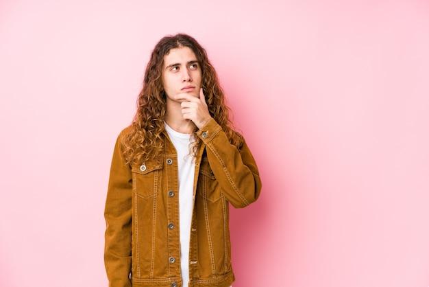 Młody mężczyzna z długimi włosami pozowanie na białym tle, patrząc z ukosa z wyrazem wątpliwości i sceptycyzmu