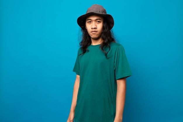 Młody mężczyzna z długimi włosami w kapeluszu z poważną twarzą odizolowaną na niebieskim tle