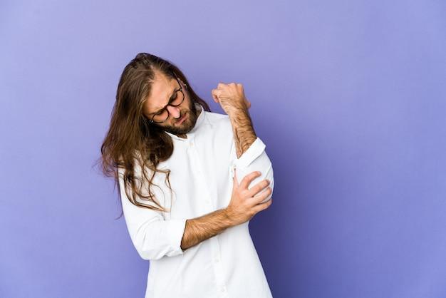 Młody mężczyzna z długimi włosami wygląda jak masujący łokieć, cierpiący po złym ruchu