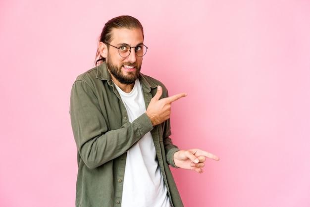 Młody mężczyzna z długimi włosami wygląda na zszokowanego, wskazując palcami wskazującymi na miejsce.
