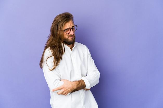 Młody mężczyzna z długimi włosami wygląda podejrzanie, niepewnie, badając cię.