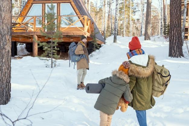 Młody mężczyzna z dużym plecakiem stojący w lesie na tle wiejskiego domu i patrzący na zbliżającą się do niego żonę i córkę