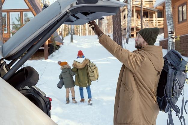 Młody mężczyzna z dużym plecakiem zamyka pokrywę bagażnika samochodu, stojąc naprzeciw swojej żony i córki zmierzającej w kierunku wiejskiego domu