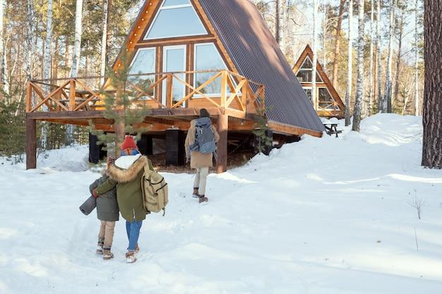 Młody mężczyzna z dużym plecakiem zmierza w kierunku wiejskiego domu, podczas gdy jego żona i ich córeczka w ciepłych zimowych strojach podążają za nim