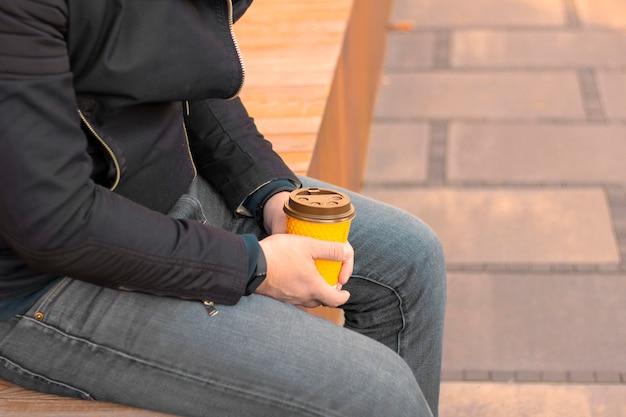 Młody mężczyzna z filiżanką kawy w dłoniach siedzi na ulicy trzymając papierowy kubek z kawą