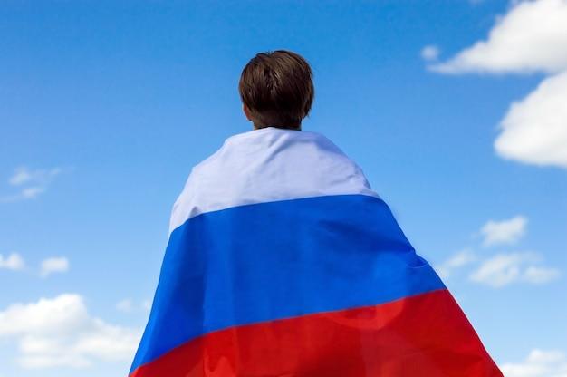Młody mężczyzna z flagą rosji stoi plecami