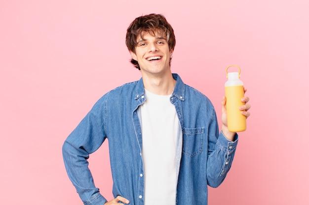 Młody mężczyzna z gładko uśmiechniętym radośnie z ręką na biodrze i pewny siebie