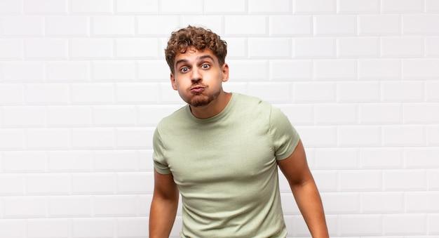 Młody mężczyzna z głupkowatym, szalonym, zaskoczonym wyrazem twarzy, nadymającymi się policzkami, czującym się wypchany, gruby i pełen jedzenia