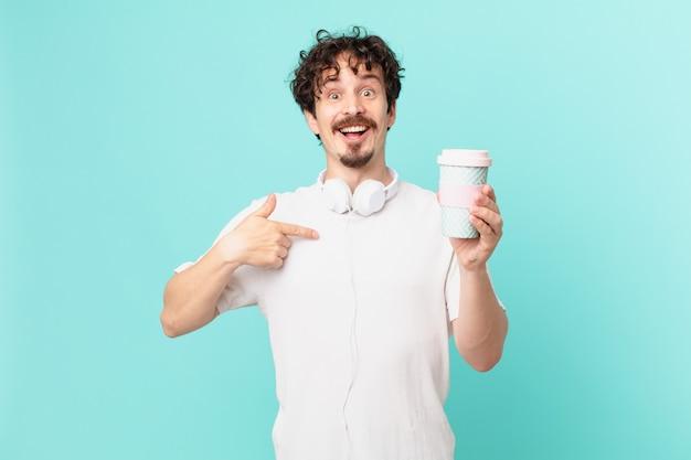 Młody mężczyzna z kawą czuje się szczęśliwy i wskazuje na siebie z podekscytowaniem