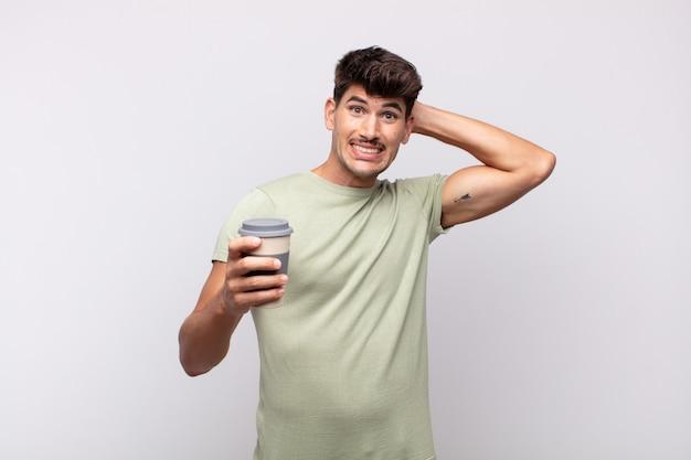 Młody mężczyzna z kawą czuje się zestresowany, zmartwiony, niespokojny lub przestraszony