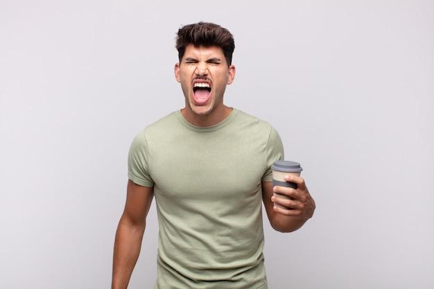 Młody mężczyzna z kawą krzyczący agresywnie, wyglądający na bardzo złego, sfrustrowanego, oburzonego lub zirytowanego, krzyczący nie