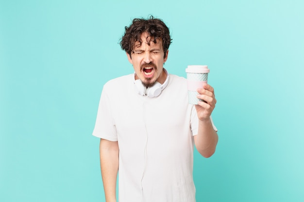 Młody mężczyzna z kawą krzyczy agresywnie, wygląda na bardzo rozgniewanego