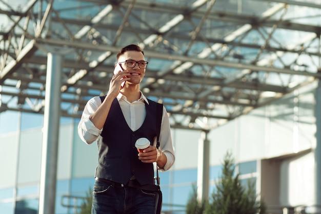 Młody mężczyzna z kawą na wynos i smartfonem idący obok
