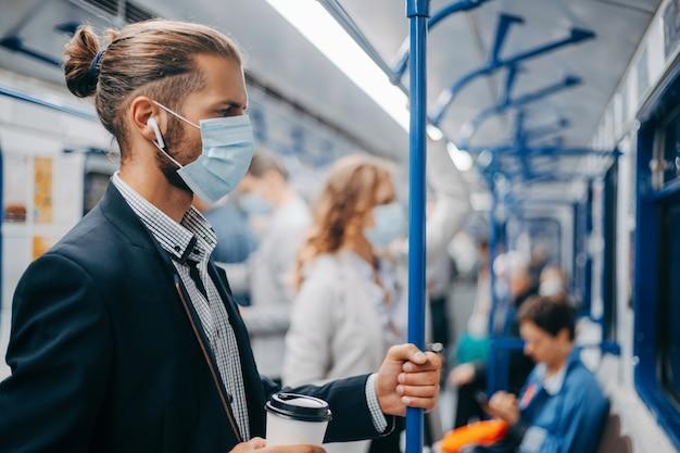 Młody mężczyzna z kawą na wynos stojący w wagonie metra