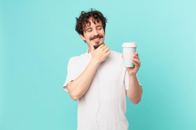 Młody mężczyzna z kawą uśmiechający się ze szczęśliwym, pewnym siebie wyrazem twarzy z ręką na brodzie