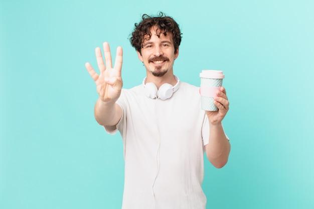 Młody mężczyzna z kawą uśmiechnięty i wyglądający przyjaźnie, pokazujący cyfrę cztery