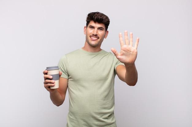 Młody mężczyzna z kawą uśmiechnięty i wyglądający przyjaźnie, pokazujący cyfrę piątą lub piątą z ręką do przodu, odliczający w dół