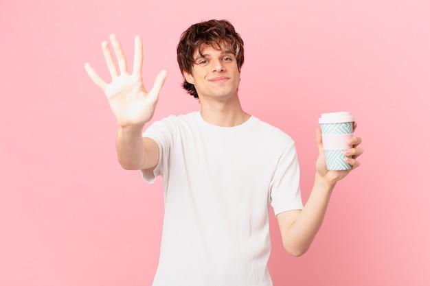 Młody mężczyzna z kawą uśmiechnięty i wyglądający przyjaźnie, pokazujący numer pięć