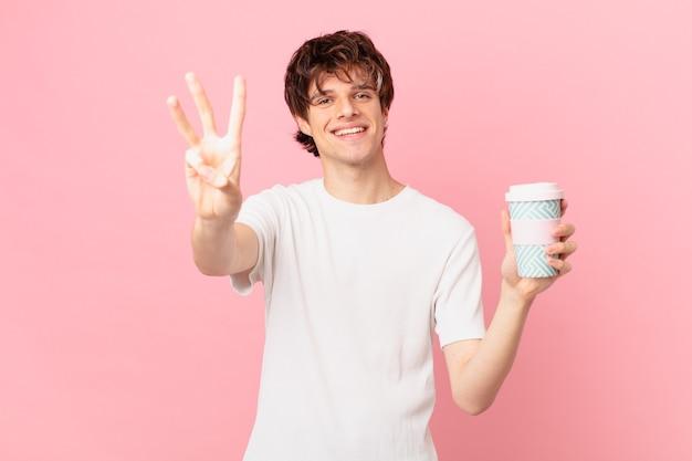 Młody mężczyzna z kawą uśmiechnięty i wyglądający przyjaźnie, pokazujący numer trzy