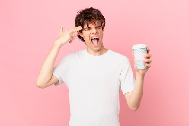 Młody mężczyzna z kawą wyglądający na niezadowolonego i zestresowanego, gest samobójczy, który robi znak pistoletu