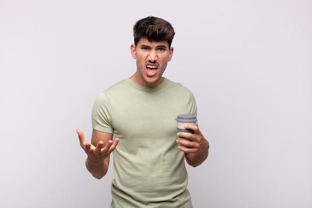 Młody mężczyzna z kawą wyglądający na złego, zirytowanego i sfrustrowanego krzyczącego wtf
