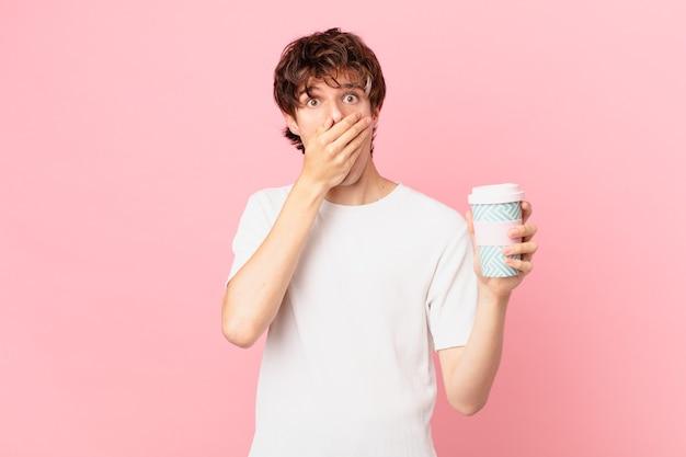 Młody mężczyzna z kawą zakrywającą usta dłońmi z szokiem